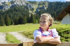 Entzückendes bayerisches Mädchen in einer schönen Berglandschaft Stockbilder