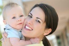 Entzückendes blaues gemustertes Baby mit Mamma lizenzfreie stockfotografie