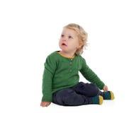 Entzückendes blondes Baby, das auf dem Boden sitzt Stockfoto