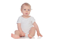 Entzückendes blondes Baby in der Unterwäsche, die auf dem Boden sitzt Stockbild