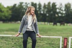 entzückendes blondes Kind, das auf Zaun sitzt Lizenzfreie Stockbilder