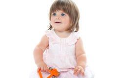 Entzückendes blondes Kind, das mit einem Geklapper spielt Stockfoto