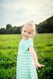 Entzückendes blondes kleines Mädchen mit unverschämtem Lächeln, draußen Stockfotografie
