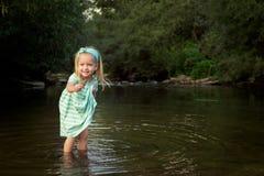 Entzückendes blondes Mädchen, das im Fluss, Erforschungskonzept spielt Lizenzfreies Stockbild