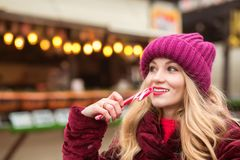 Entzückendes blondes Mädchen in der roten Strickmütze, die mit Zuckerstange a aufwirft Lizenzfreie Stockfotos