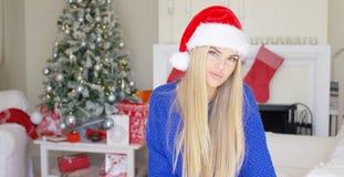 Entzückendes blondes Mädchen im Weihnachtshut in ihrem Haus Lizenzfreie Stockbilder