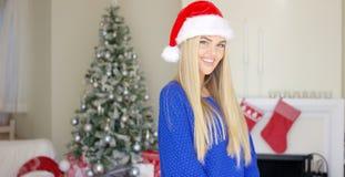 Entzückendes blondes Mädchen im Weihnachtshut in ihrem Haus Lizenzfreies Stockbild