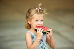 Entzückendes blondes Mädchen isst eine Scheibe der Wassermelone draußen Stockfotos