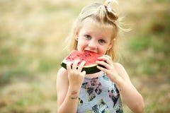 Entzückendes blondes Mädchen isst eine Scheibe der Wassermelone draußen Lizenzfreies Stockbild