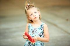Entzückendes blondes Mädchen isst eine Scheibe der Wassermelone draußen Lizenzfreies Stockfoto