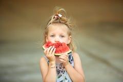 Entzückendes blondes Mädchen isst eine Scheibe der Wassermelone draußen Stockfoto