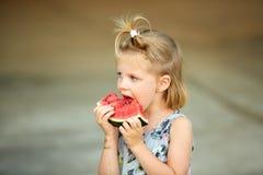 Entzückendes blondes Mädchen isst eine Scheibe der Wassermelone draußen Stockfotografie
