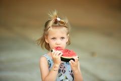 Entzückendes blondes Mädchen isst eine Scheibe der Wassermelone draußen Lizenzfreie Stockfotografie