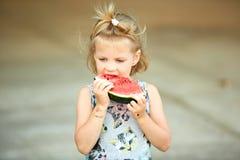 Entzückendes blondes Mädchen isst eine Scheibe der Wassermelone draußen Stockbilder