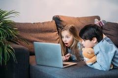 Entzückendes entsetztes Mädchen und Junge, der Laptop verwendet Lizenzfreie Stockfotografie