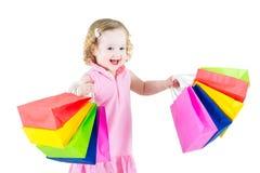 Entzückendes gelocktes Mädchen nach Verkauf mit ihren bunten Taschen Stockfoto