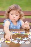 Entzückendes glückliches kleines Kind, das mit Puzzlespiel spielt Stockfoto