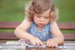 Entzückendes glückliches kleines Kind, das mit Puzzlespiel spielt Stockbilder
