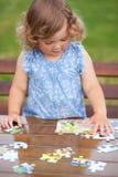 Entzückendes glückliches kleines Kind, das mit Puzzlespiel spielt Stockbild