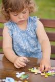 Entzückendes glückliches kleines Kind, das mit Puzzlespiel spielt Stockfotografie