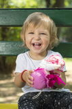 Entzückendes jähriges Baby, das auf einer Bank mit einer Puppe I sitzt Lizenzfreie Stockfotos