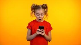 Entzückendes jugendlich Mädchen überrascht mit dem Lösen von Aufgabe im pädagogischen App auf Smartphone lizenzfreie stockfotografie