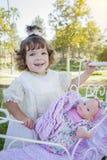 Entzückendes junges Baby, das mit Baby - Puppe und Wagen spielt Stockfotografie
