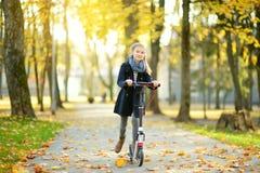 Entzückendes junges Mädchen, das ihren Roller in einem Stadtpark am sonnigen Herbstabend reitet Hübsches jugendliches Kind, das e lizenzfreies stockbild