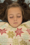 Entzückendes junges Mädchen, das unter einer Schneeflockendecke schläft Stockfotos