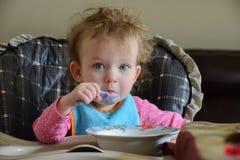 Entzückendes kaukasisches Baby sitzt auf dem Tisch, hält einen Löffel und isst Baby ist sehr überrascht Säuglings-` s hören wird  Stockfotografie