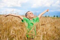 Entzückendes Kind auf einem Weizengebiet Stockbilder
