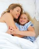 Entzückendes Kind, das mit ihrer Mutter umarmt stockbild