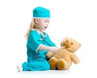 Entzückendes Kind gekleidet als Doktor, der mit Spielzeug spielt stockbild