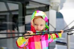 Entzückendes Kind im bunten Mantel, der Wasser vom Reisenboot betrachtet Stockfotografie