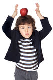 Entzückendes Kind mit einem Apfel im Kopf Lizenzfreies Stockfoto