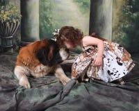 Entzückendes Kind und ihr Bernhardiner-Welpen-Hund Stockfoto