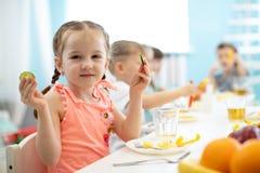 Entzückendes Kindermädchen, das Gemüse im Kindergarten isst stockfoto