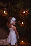 Entzückendes Kindermädchen im weißen Kleid und im Stirnband, die Buch im Sommerabendgarten verziert mit Lichtern hält Stockfotografie
