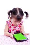 Entzückendes kleines asiatisches (thailändisches) Mädchen, das digitale Tablette am Schreibtisch verwendet lizenzfreie stockfotografie