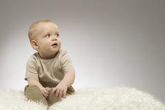Entzückendes kleines Baby, das auf der weißen Decke, Atelieraufnahme, lokalisiert auf grauem Hintergrund, reizendes Babyporträt s Stockfotografie
