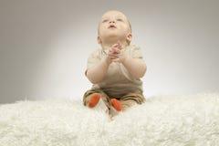Entzückendes kleines Baby, das auf der weißen Decke sitzt und oben, Atelieraufnahme, lokalisiert auf grauem Hintergrund schaut Stockbilder