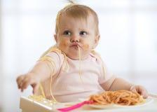 Entzückendes kleines Baby ein Jahr die Teigwaren essend Innen Lustiges Kleinkindkind mit Spaghettis Nettes Kind und gesundes Lebe lizenzfreies stockfoto