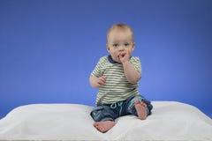 Entzückendes kleines Baby, sitzend auf der weißen Decke, Atelieraufnahme, auf blauem Hintergrund Stockfoto