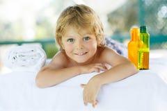 Entzückendes kleines blondes Kind, das im Badekurort mit Haben von Massage sich entspannt Stockfotos