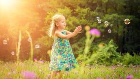Entzückendes kleines blondes Mädchen, das den Spaß spielt mit Seifenblasen hat Stockfotografie
