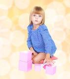 Entzückendes kleines blondes Mädchen sitzt auf Stockfotos