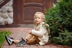 Entzückendes kleines gelocktes blondes Mädchen in der Beige strickte Strickjacke smilin lizenzfreies stockbild