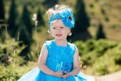 Entzückendes kleines Kindermädchen auf Gras auf Wiese Grüner Naturhintergrund des Sommers Lizenzfreie Stockfotos
