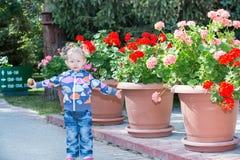 Entzückendes kleines Kindermädchen im Park nahe Blumenbeet am Sommertag Lizenzfreies Stockfoto