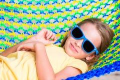 Entzückendes kleines Mädchen auf den tropischen Ferien, die in der Hängematte sich entspannen Stockfotografie